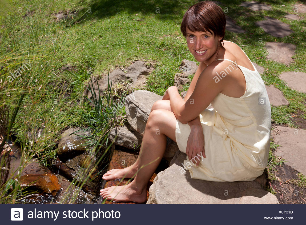 Smiling woman sitting with feet in stream looking at camera - Stock Image
