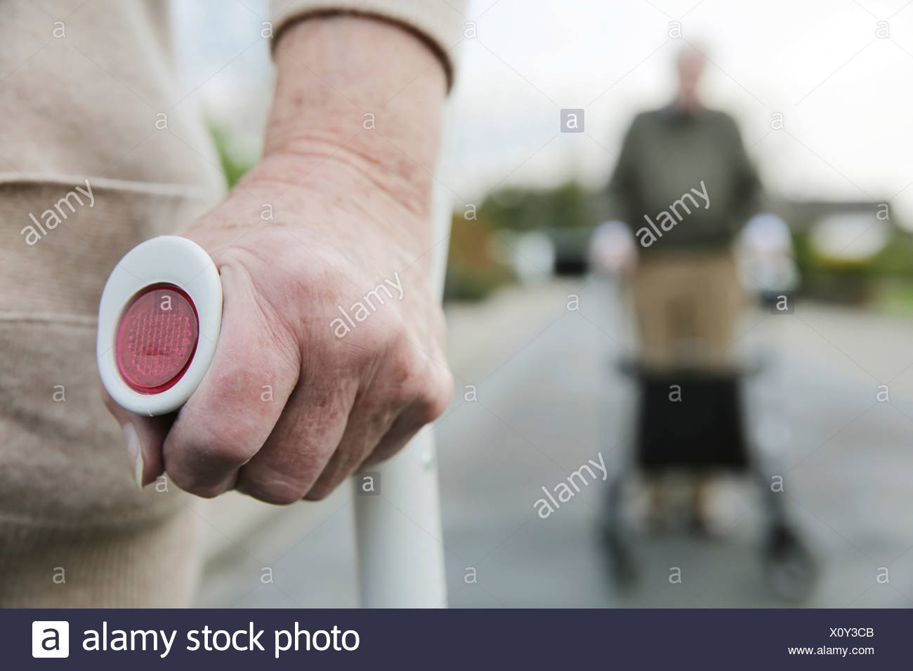 Senior couple with wheeled walker and crutch - Stock Image