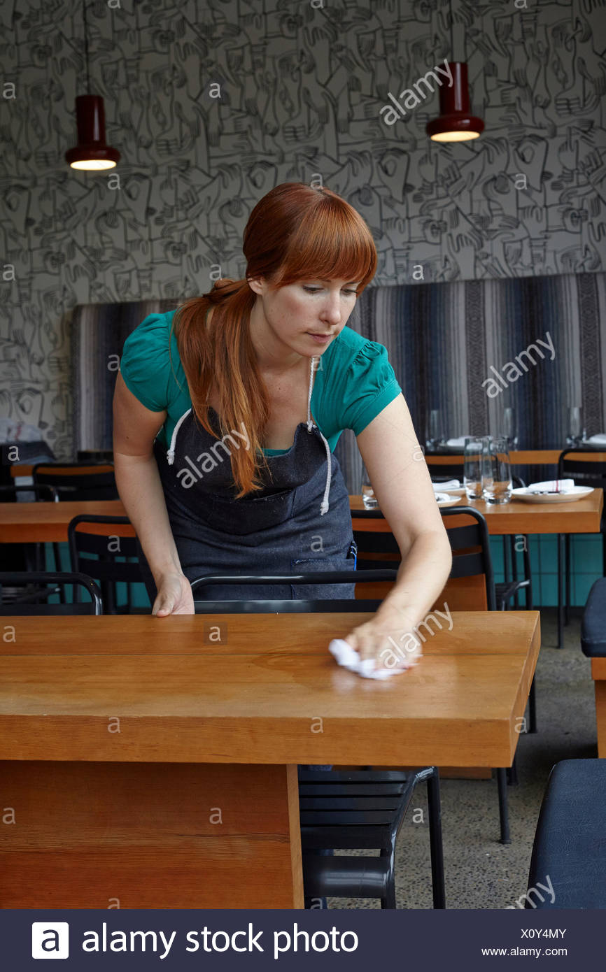 Mid adult woman cleaning table in restaurant - Stock Image