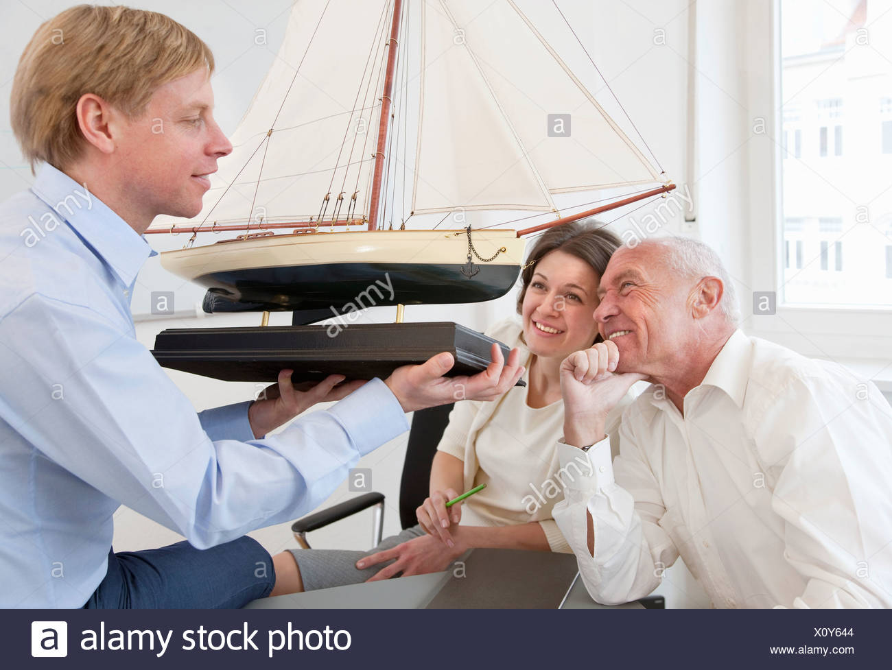 Businesspeople looking at model ship - Stock Image