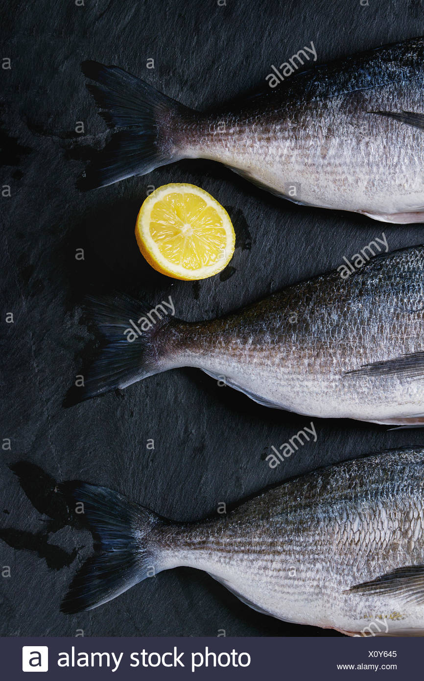 Three tails of raw bream fish with lemon on stone slate black textured background. With copy space. Top view - Stock Image