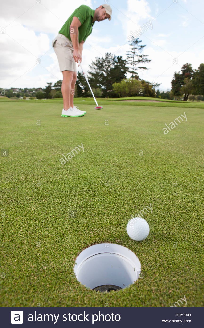 Young male golfer playing the ball on the green Stock Photo