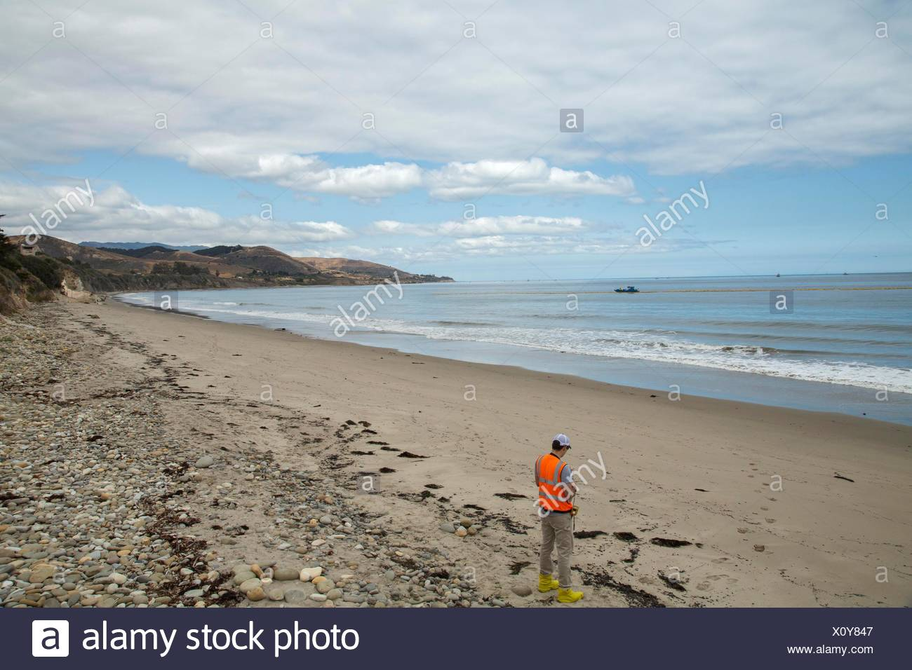 A technician hired by the oil company monitoring air quality,benzene and other hazardous contaminant levels,containment and clean up of the oil spill near Refugio State Beach. - Stock Image
