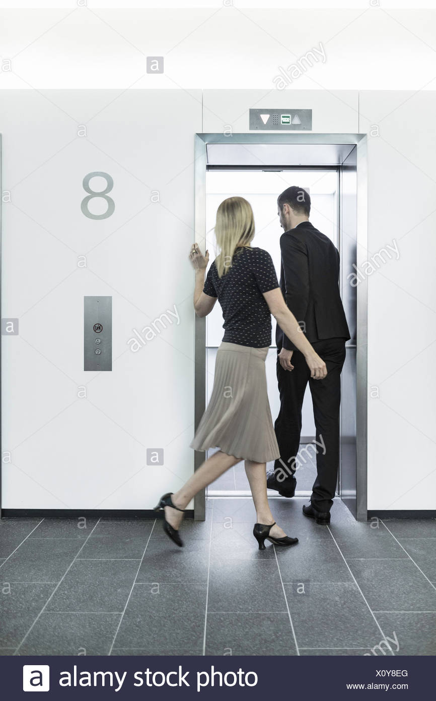 Businesspeople going into elevator - Stock Image