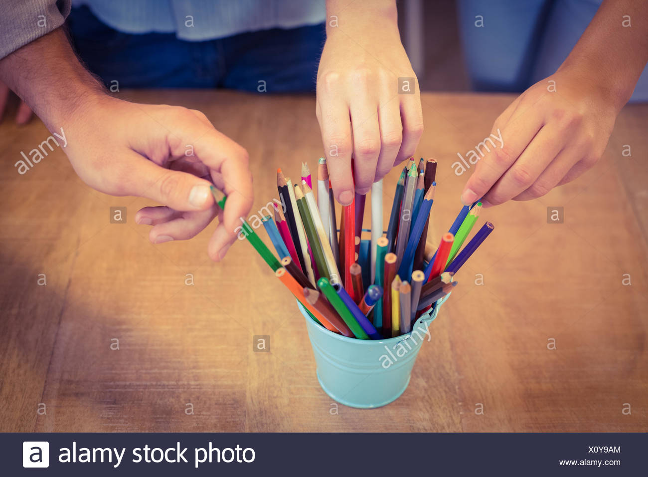 Business people choosing pencils from desk organizer - Stock Image