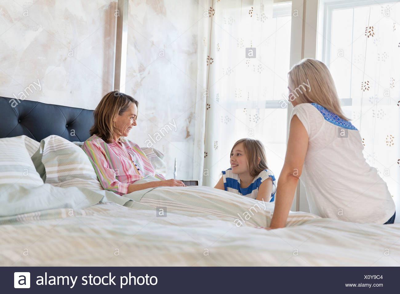 Senior woman in bed visiting with daughter and granddaughter - Stock Image