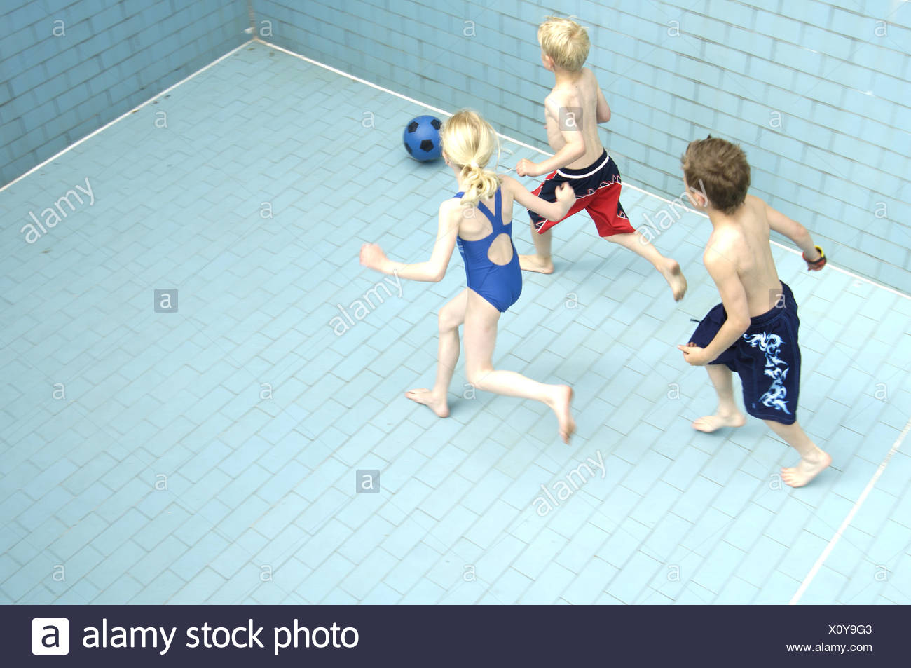 Pool empty children soccer games from above series people girls boys bath-clothing pools basin-ground tiles ball ball-game - Stock Image