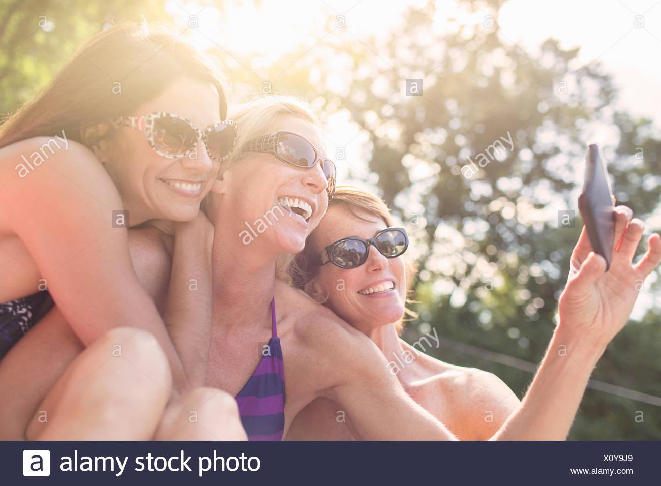 Three mature women in swimwear, taking self portrait - Stock Image