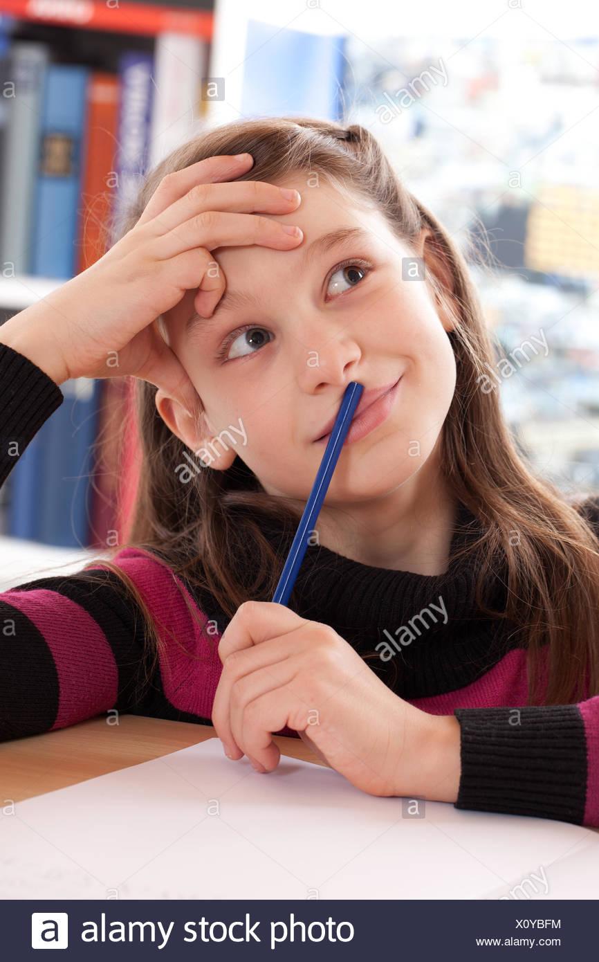 Mädchen macht Hausaufgaben und denkt nach Stock Photo