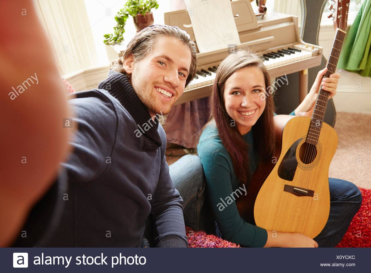 Young man taking selfie with guitarist girlfriend - Stock Image