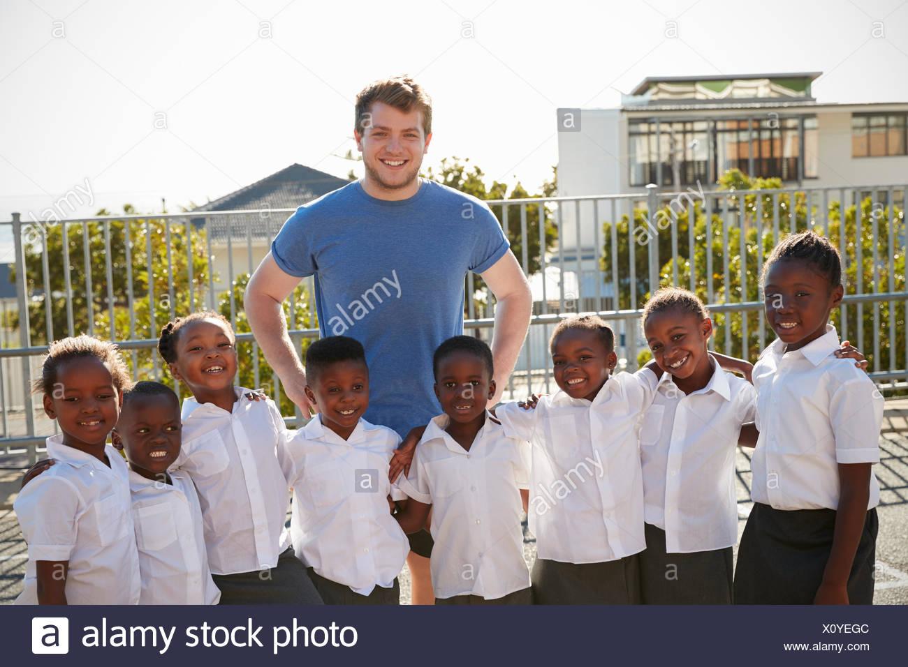 Volunteer and elementary school kids in playground, portrait - Stock Image