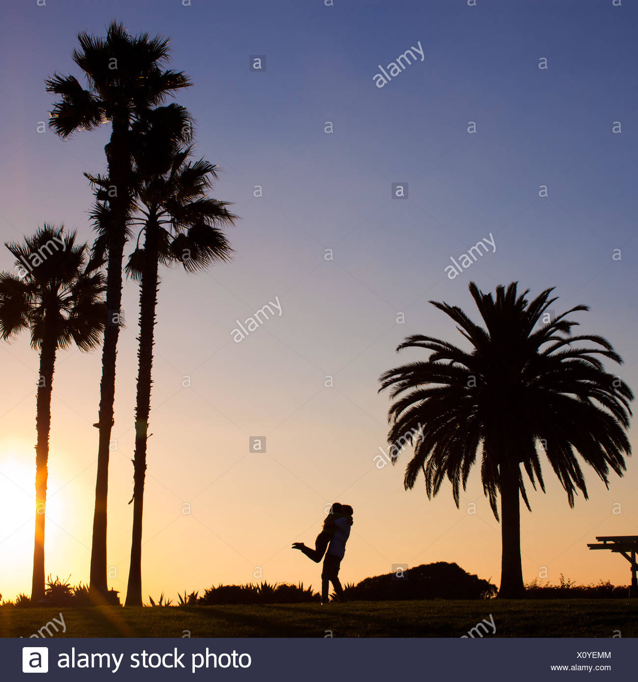 Silhouette of a man lifting his girlfriend - Stock Image