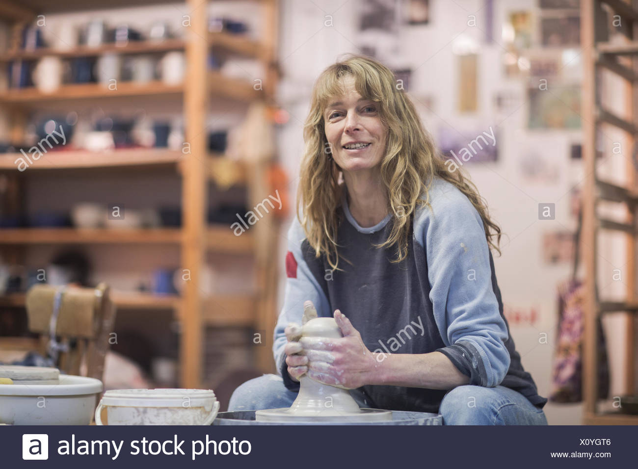 Portrait of female potter forming clay on pottery wheel - Stock Image