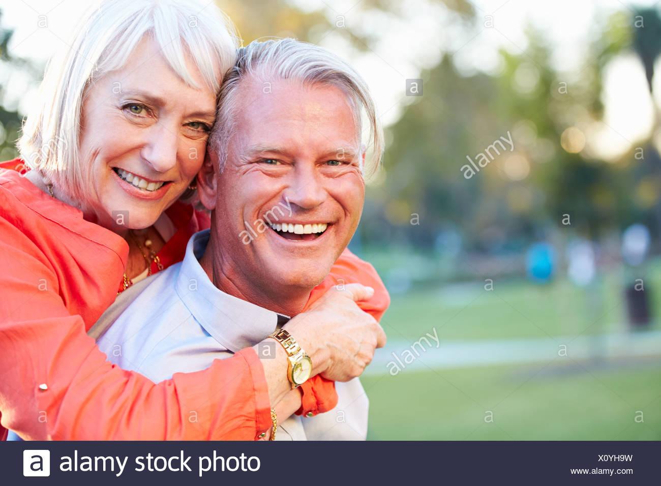 outdoor portrait of romantic mature couple in park stock photo