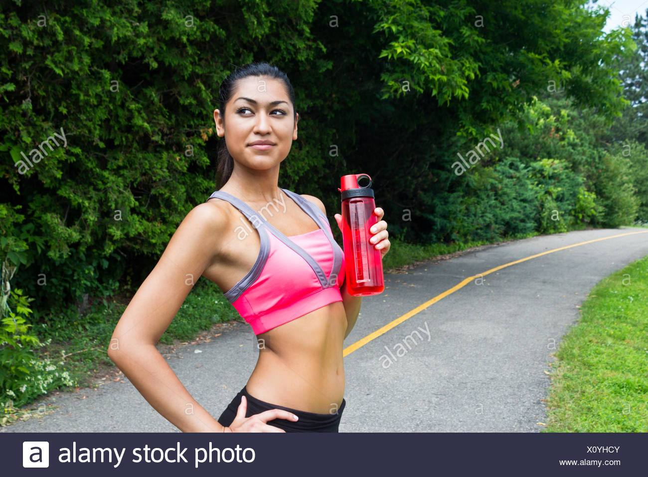Fit young woman with water bottle after running - Stock Image