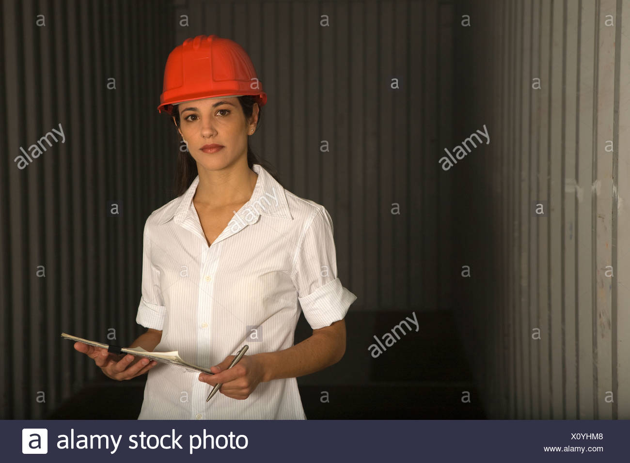 Portrait of a dock worker standing with a clipboard at a commercial dock - Stock Image