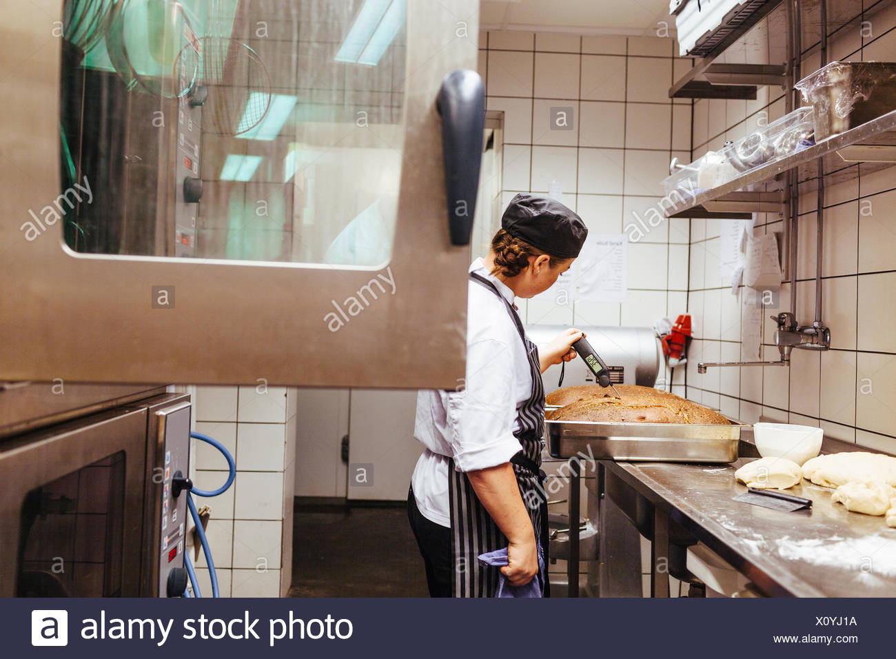 Chef checking temperature of bread in commercial kitchen - Stock Image