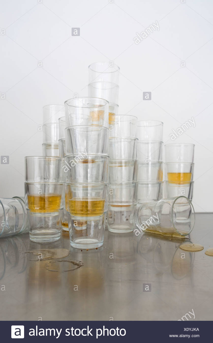 Stacks of beer glasses the morning after a party - Stock Image