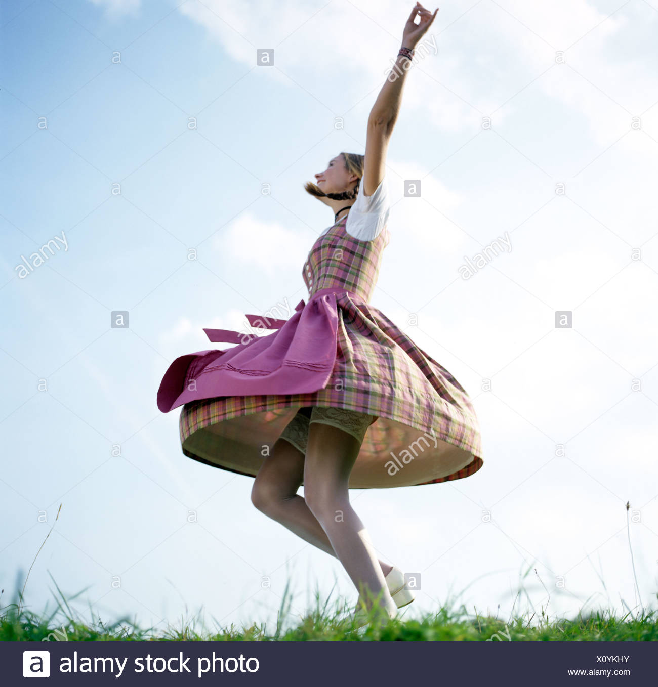 f027876079cb young woman in traditional German Bavarian dress dancing with lifted skirt