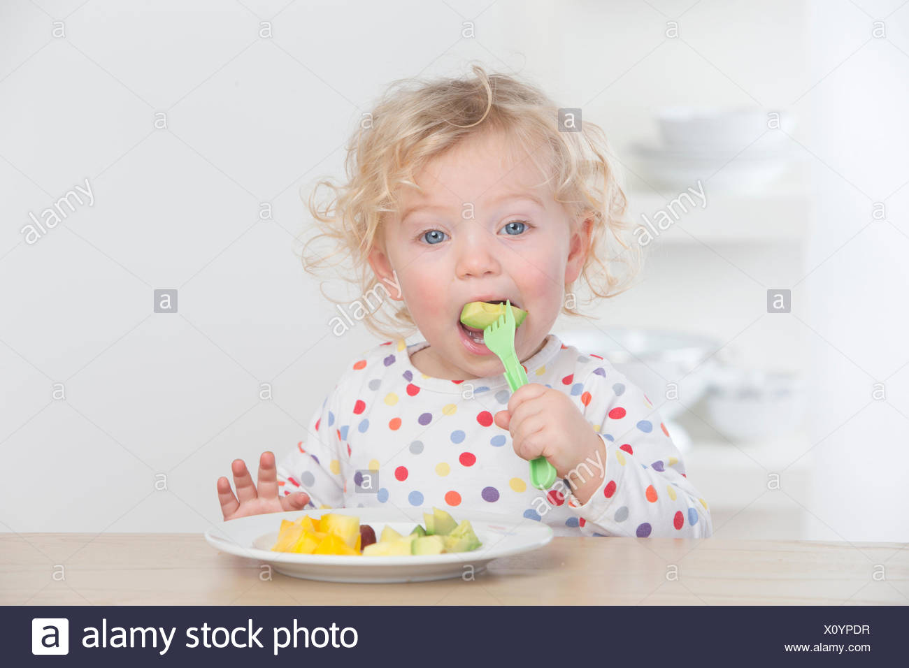 Baby eating fruit with fork - Stock Image