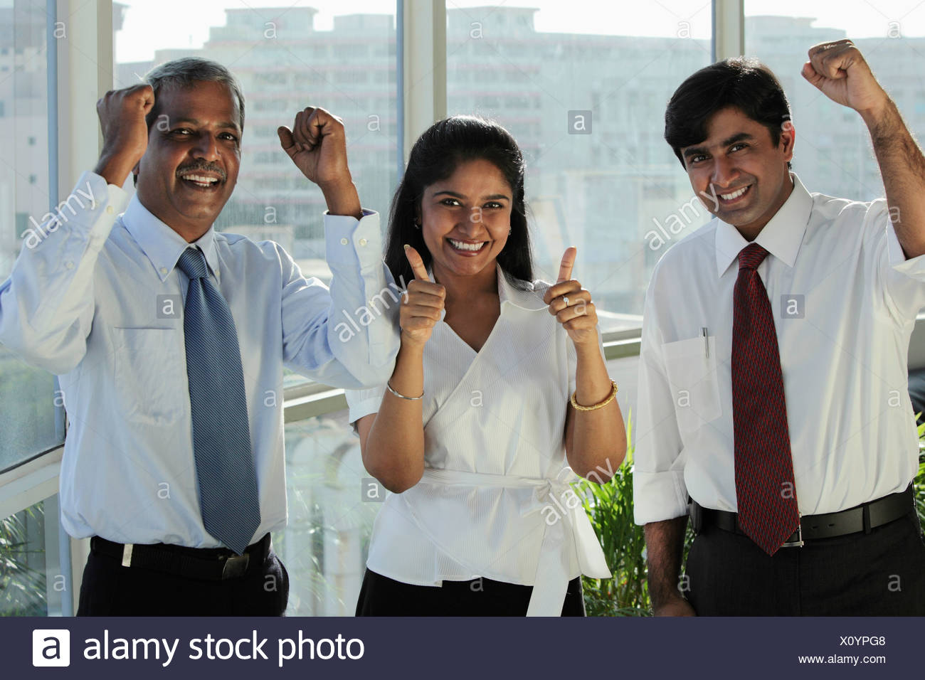 Three Indian people smiling making hand gestures - Stock Image