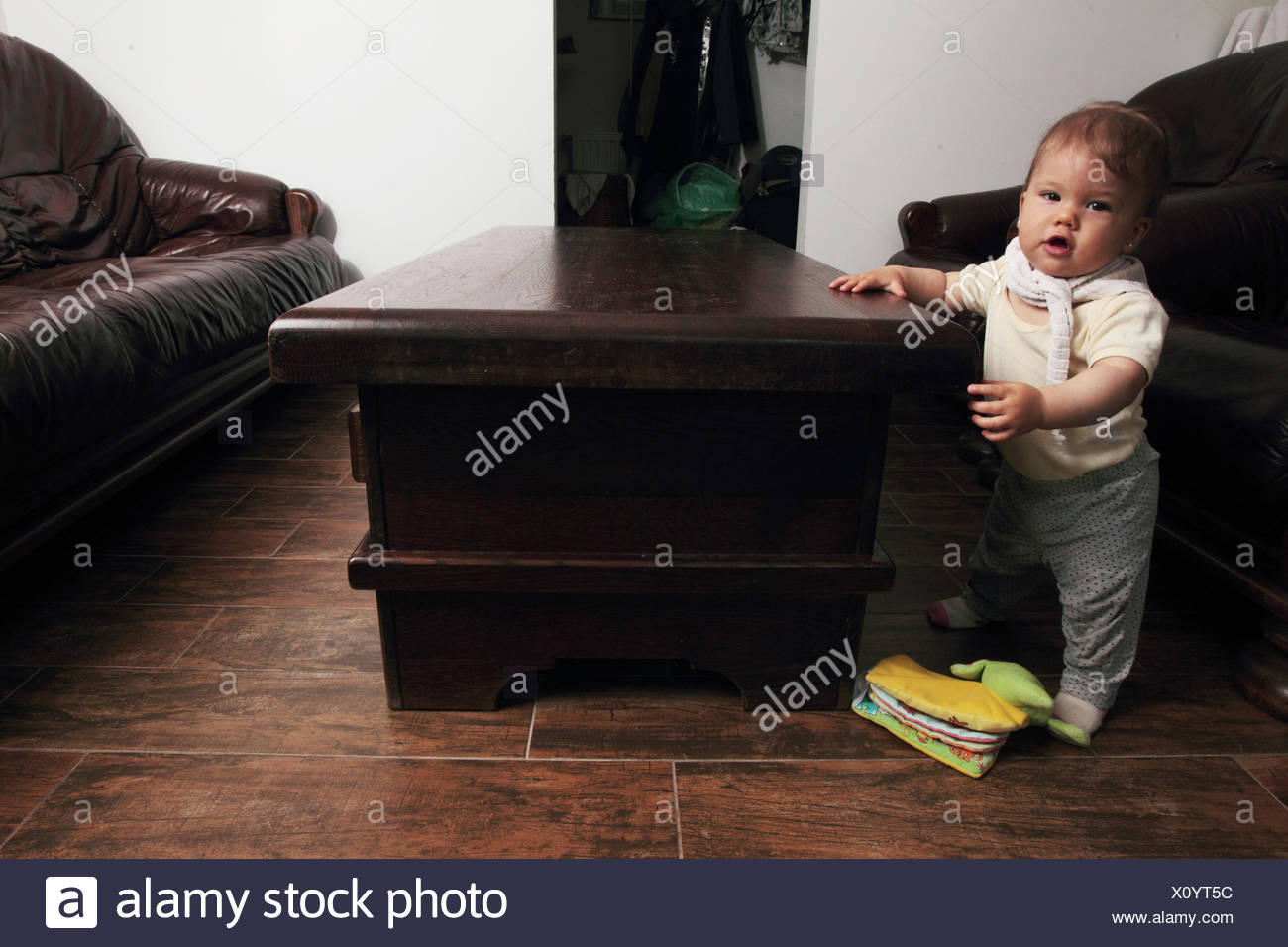 A nine-months-old baby girl standing while holding onto a coffee table. - Stock Image