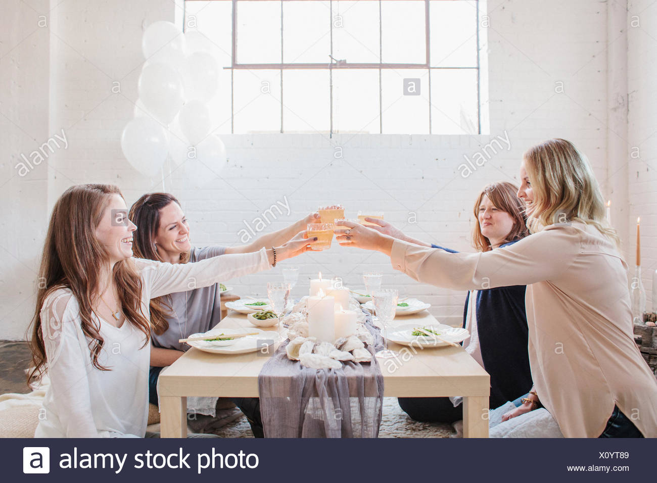 Four women seated at a low table, raising their glasses in a toast to each other. - Stock Image