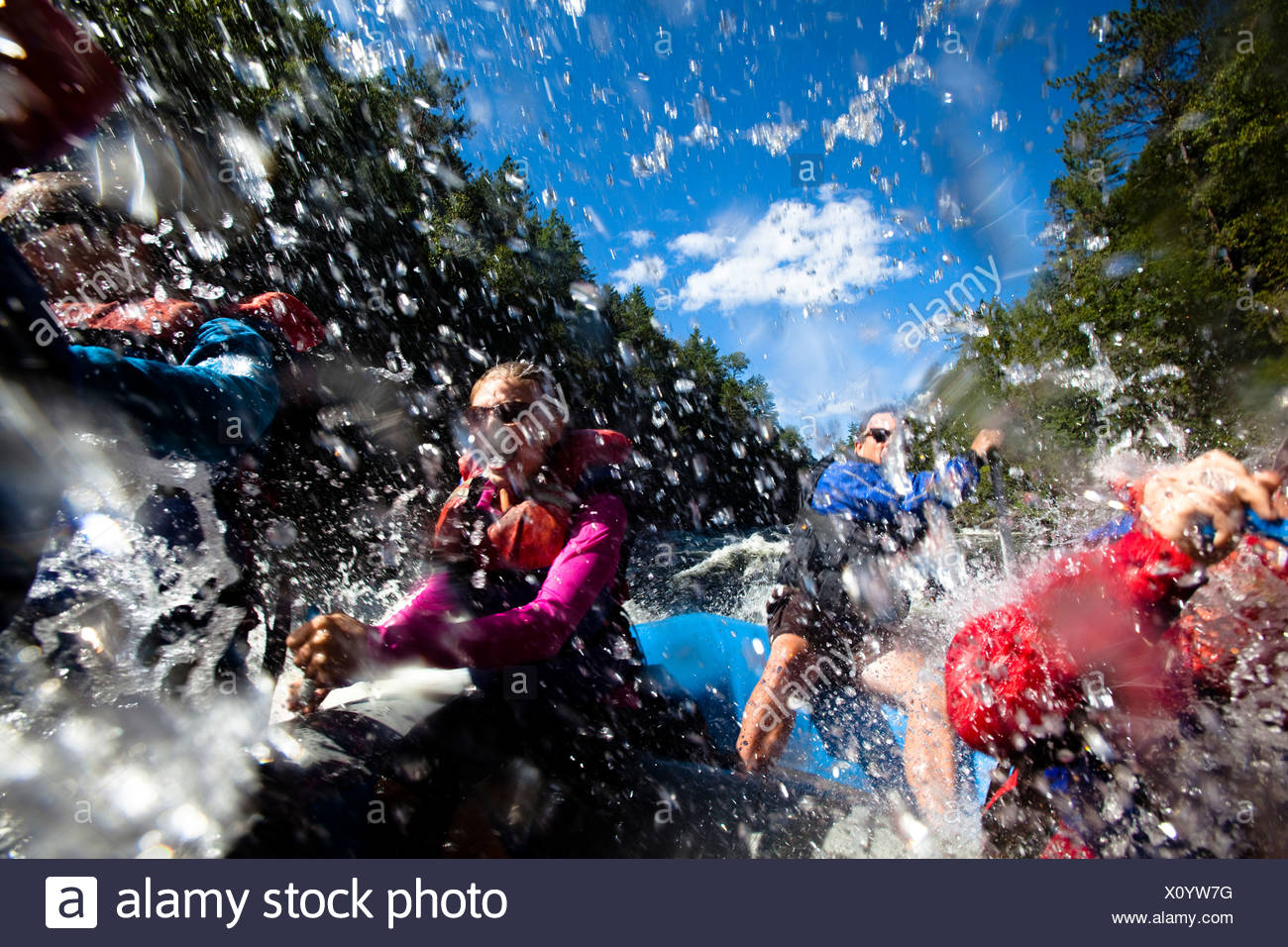 A group of adults whitewater rafting in Maine. - Stock Image