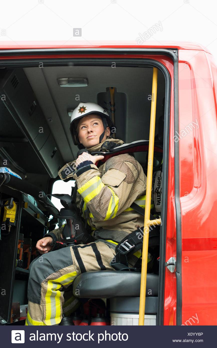 Sweden, Female firefighter in fire engine - Stock Image