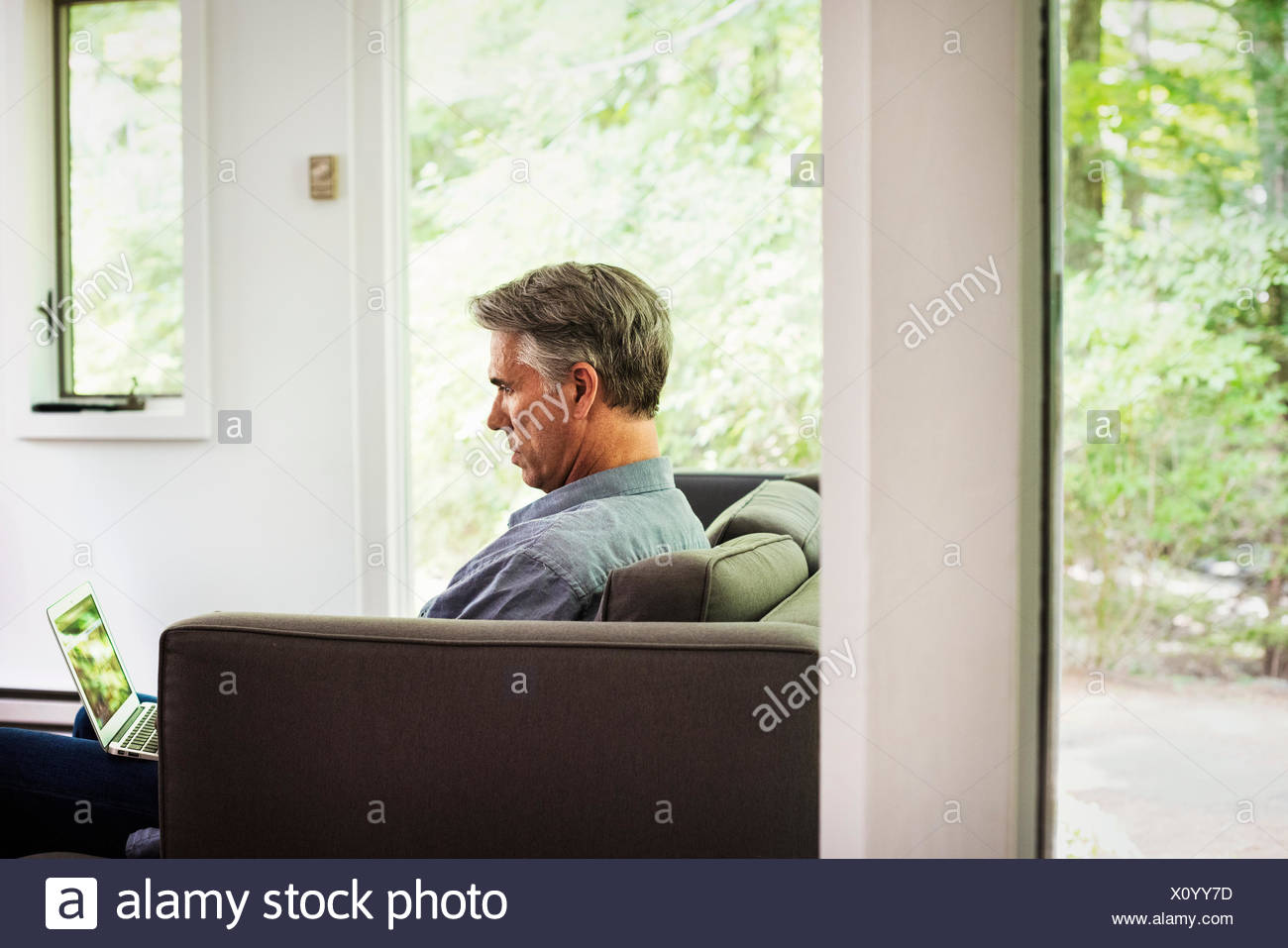 A man seated on a sofa, using a laptop. - Stock Image