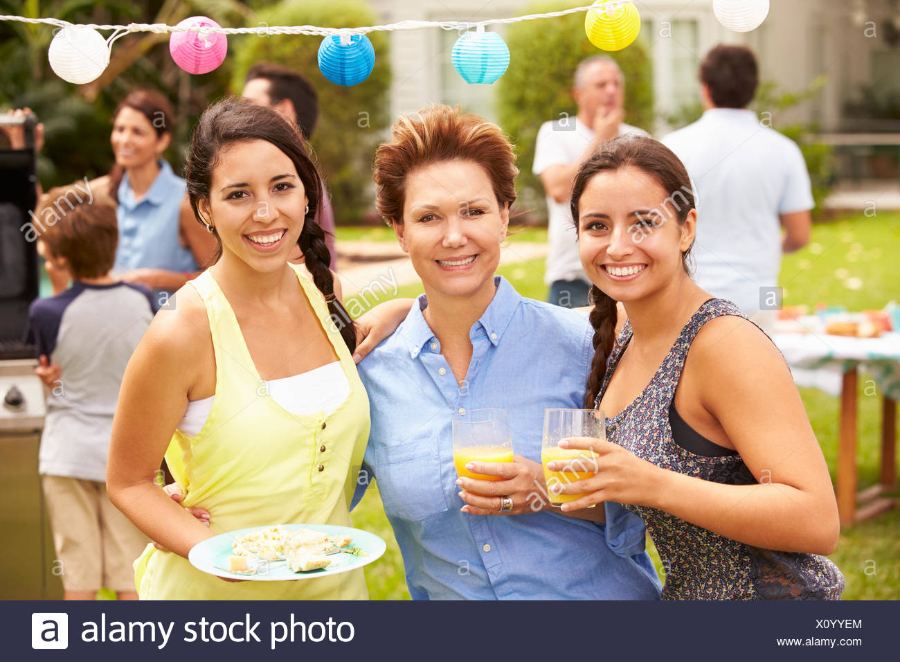 Mother With Adult Daughters Enjoying Party In Garden - Stock Image