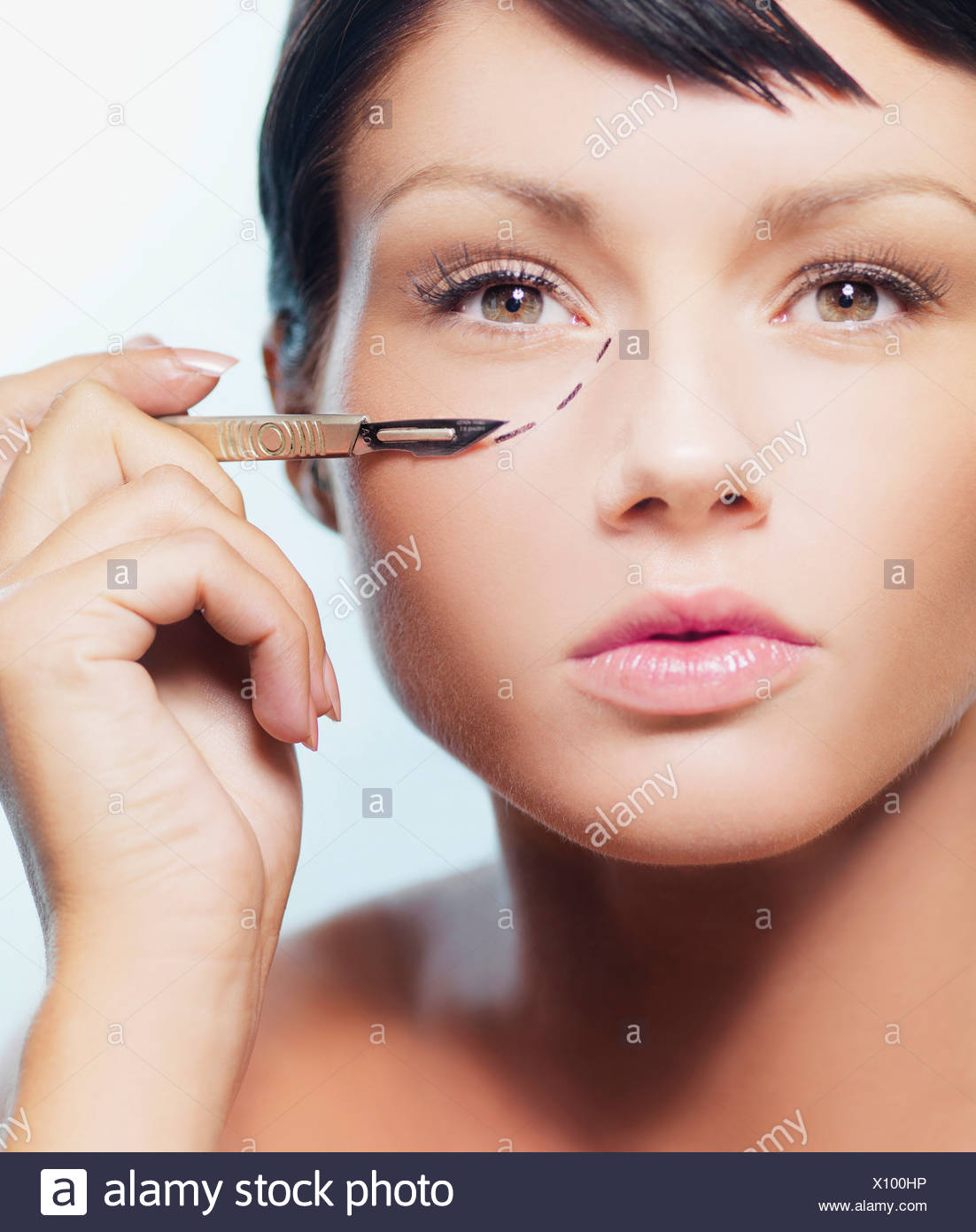 A woman with a dotted line under her eye holding a scalpel Stock Photo