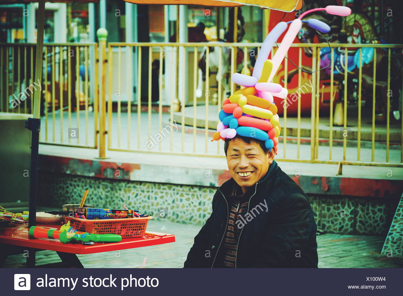 Happy Man Wearing Balloon Hat In Amusement Park - Stock Image