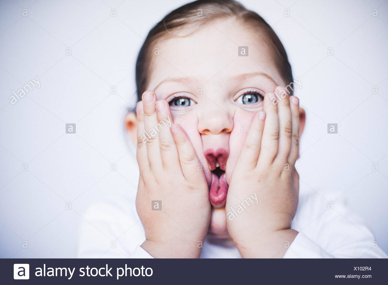 Portrait of a girl squashing her cheeks together making a funny face - Stock Image