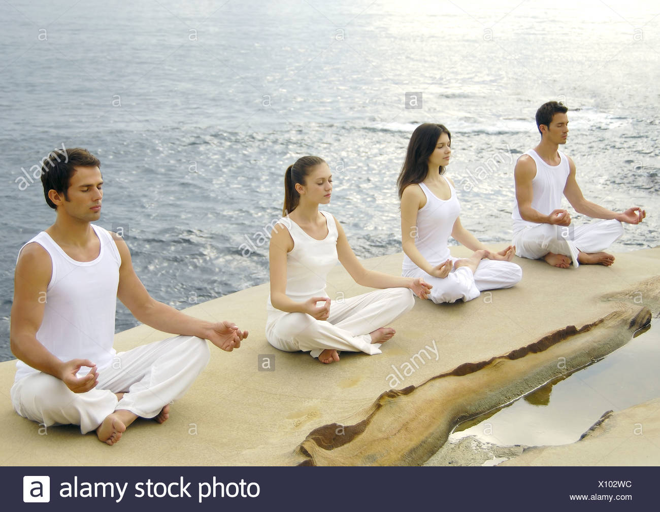 Two young men and two young women practicing yoga Stock Photo