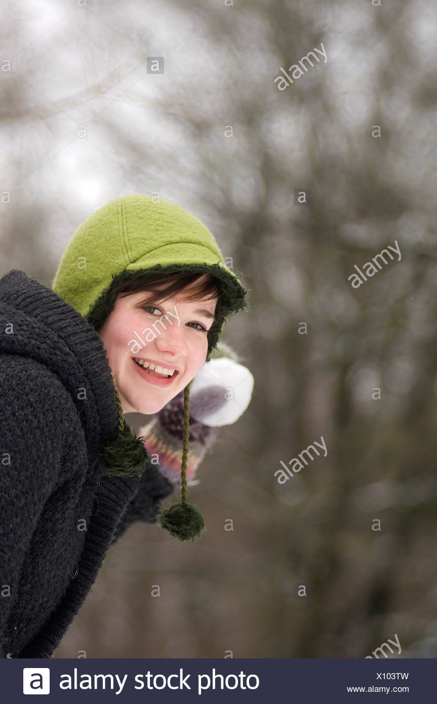 teenage girl in winter throwing snow ball - Stock Image