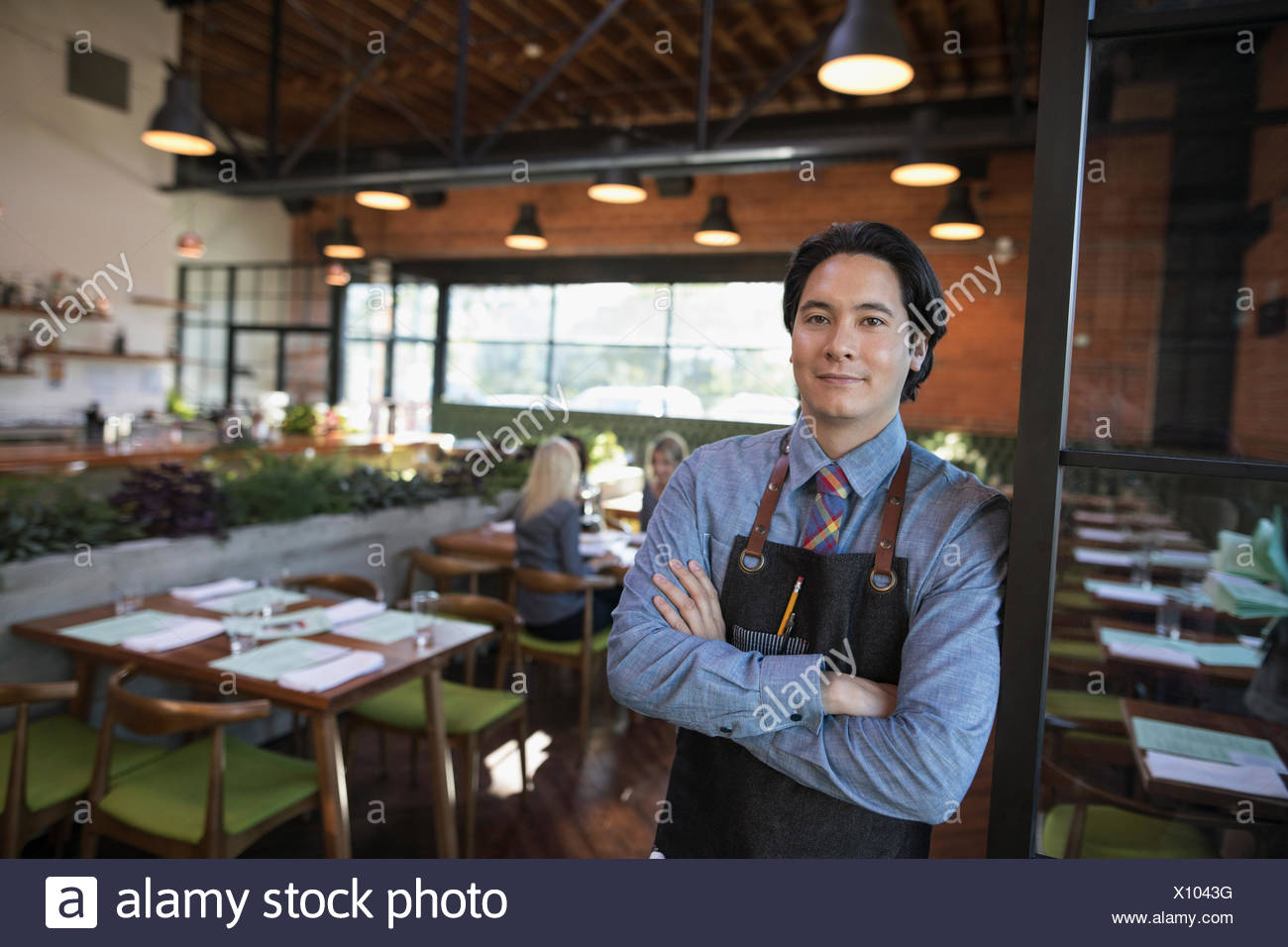 Portrait confident male server with arms crossed in restaurant - Stock Image