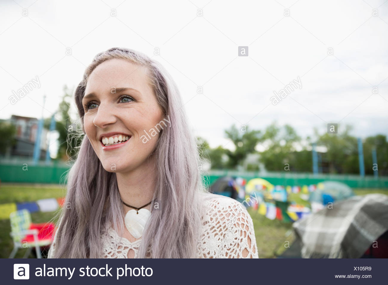 Portrait smiling young woman with chalk dyed purple hair looking away at summer music festival campsite - Stock Image