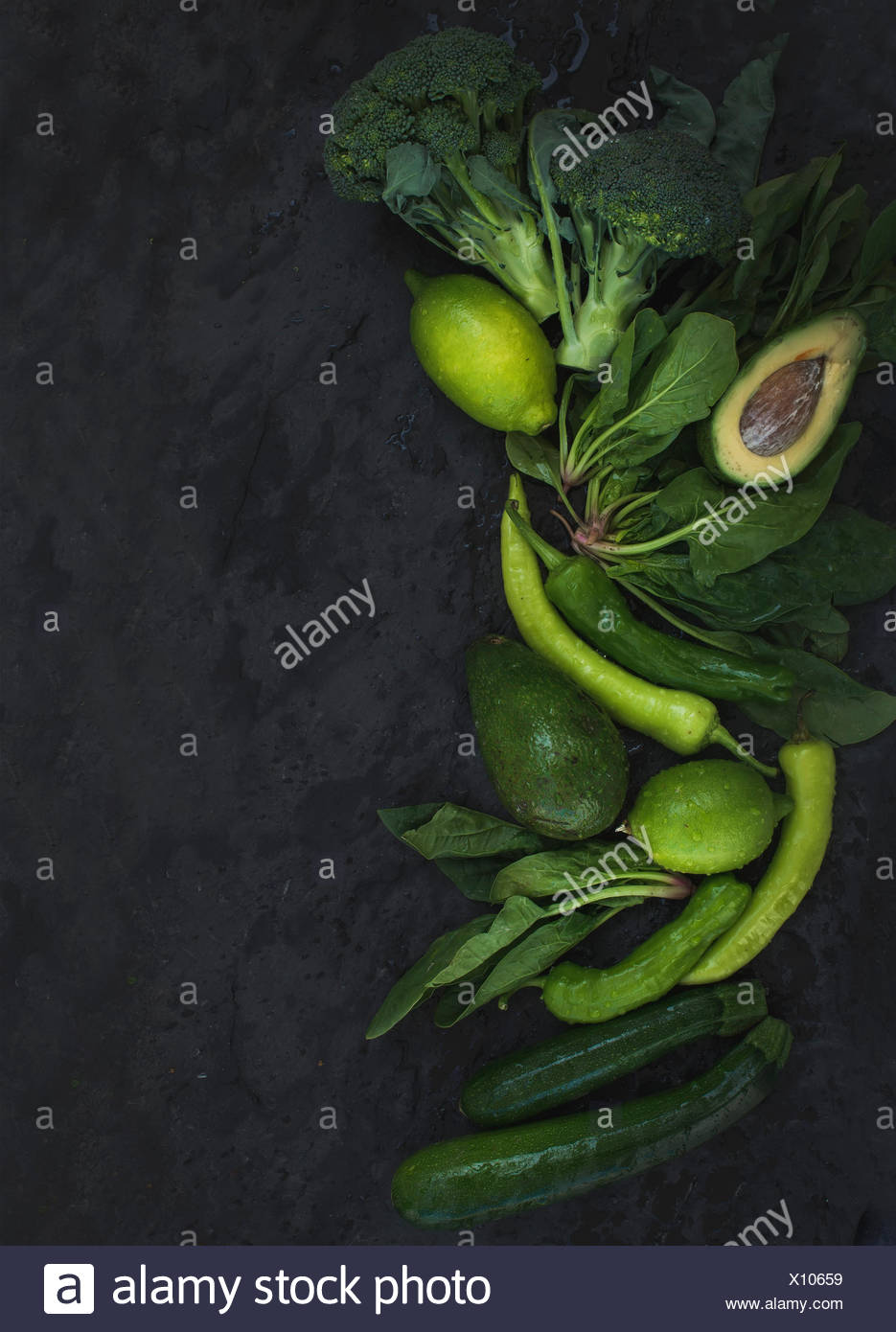 Raw green vegetables set. Broccoli avocado pepper spinach zuchcini and lime on  dark stone background top view copy space - Stock Image