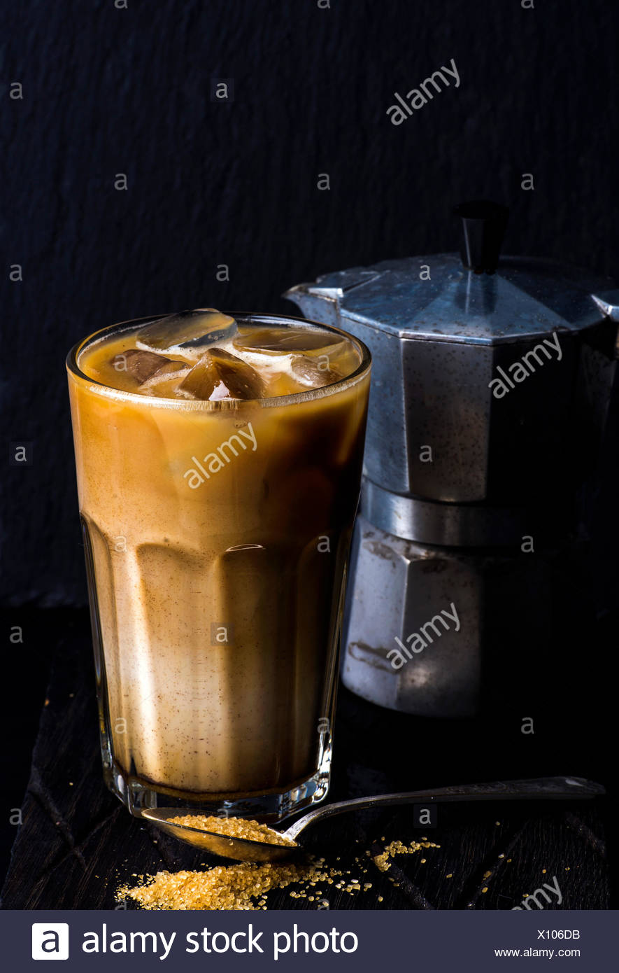 Iced coffee with milk in a tall glass, moka pot, black background, selective focus - Stock Image