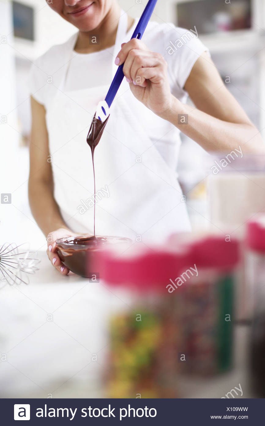 Woman pouring melted chocolate - Stock Image