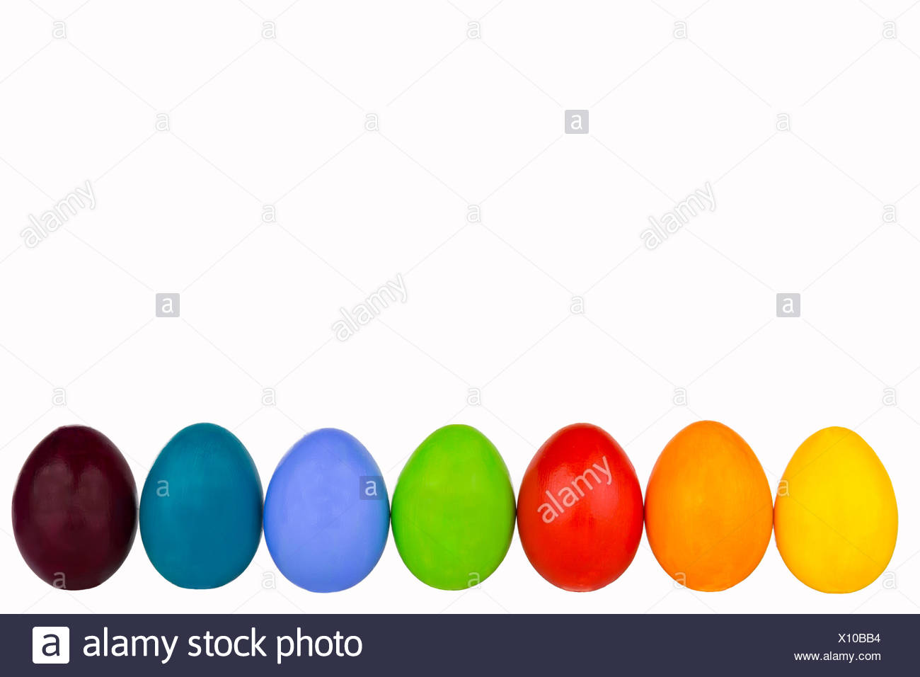 coloured easter eggs in a row - Stock Image