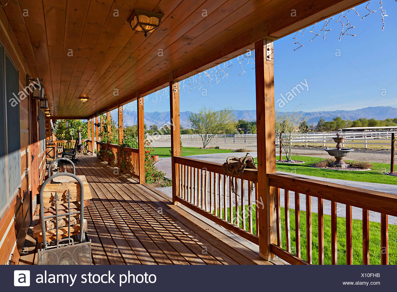 Ranch porch overlooking horse stables - Stock Image