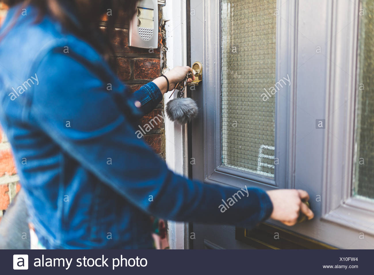 Young woman leaving house, locking front door, mid section - Stock Image