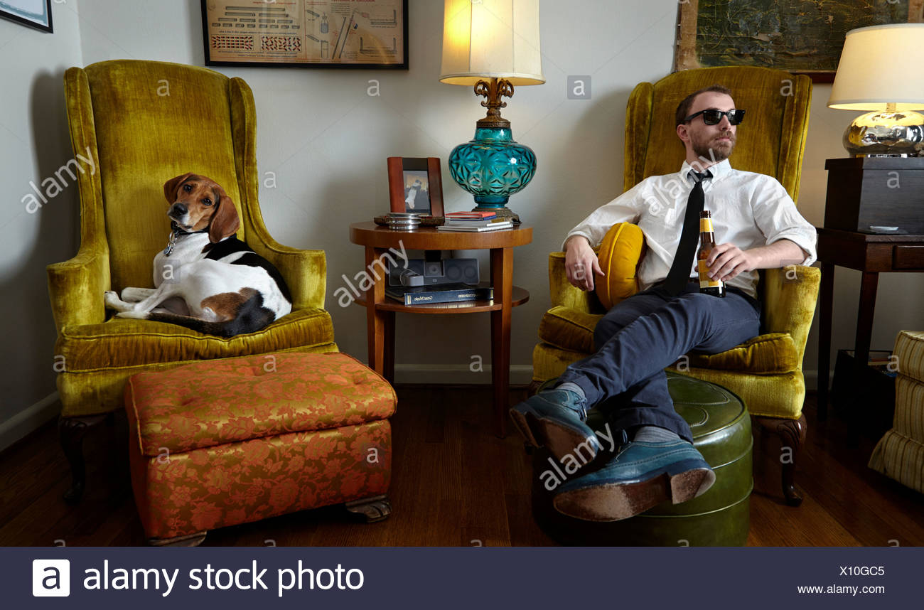 Young man and pet dog relaxing in armchair in living room - Stock Image