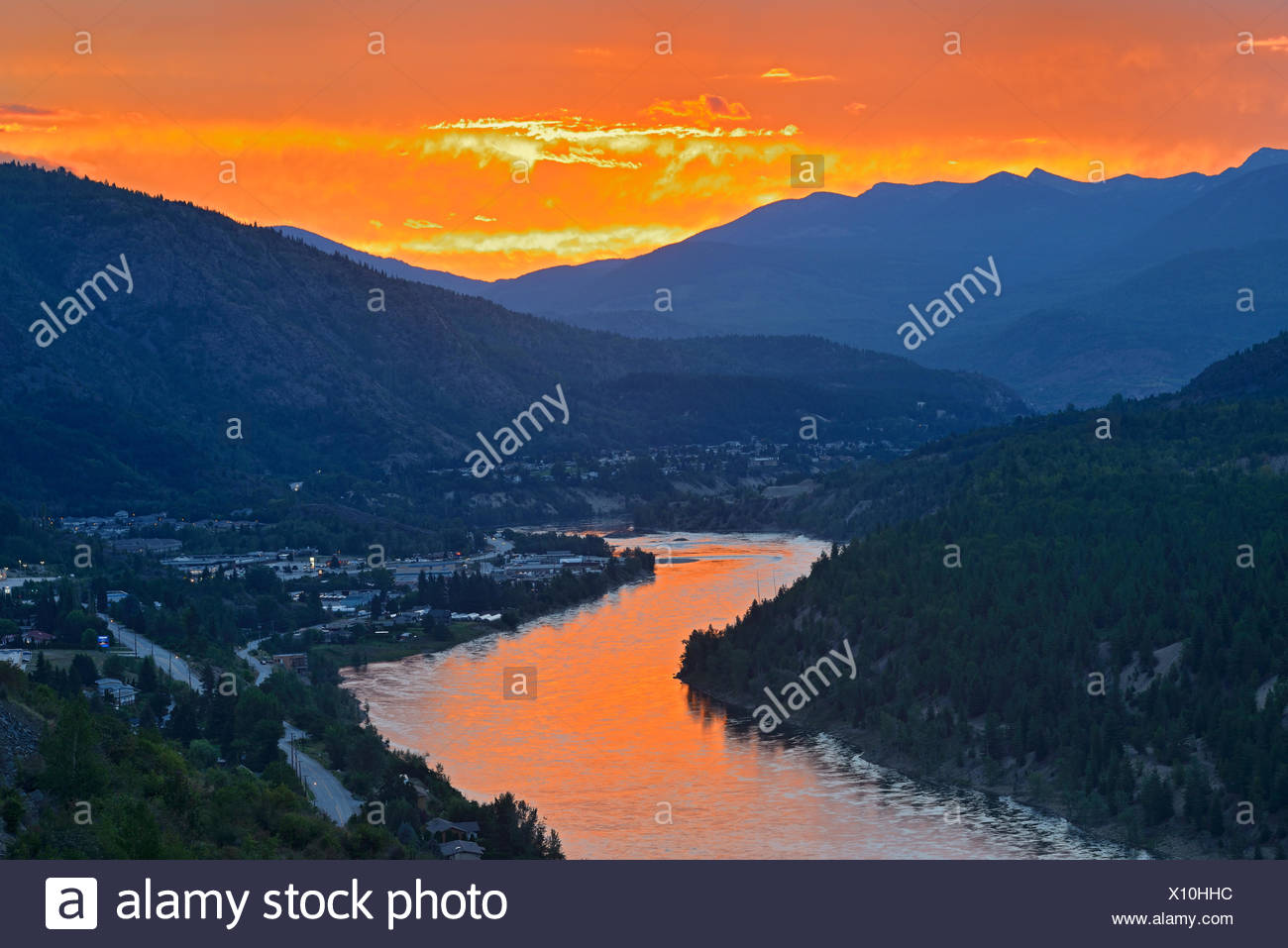 Sunset reflecting off the Columbia River in the Columbia Valley flanked by the Monashee Mountains in the West and the Selkirk Mountains in the East, Trail, British Columbia, Canada - Stock Image