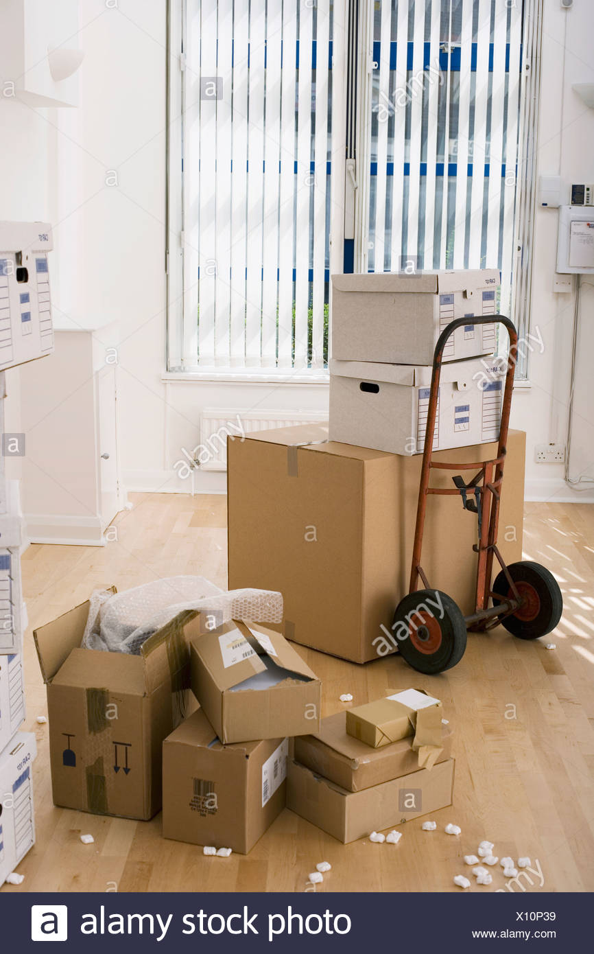 Large cardboard box on hand truck in office small boxes on wooden floor near packing foam - Stock Image