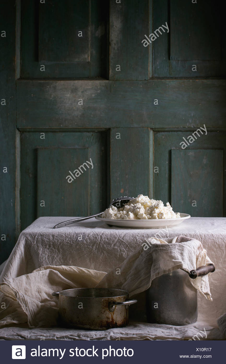 Plate of homemade cottage cheese, served with vintage aluminum pan and water-can on white tablecloth with turquoise wooden backg - Stock Image