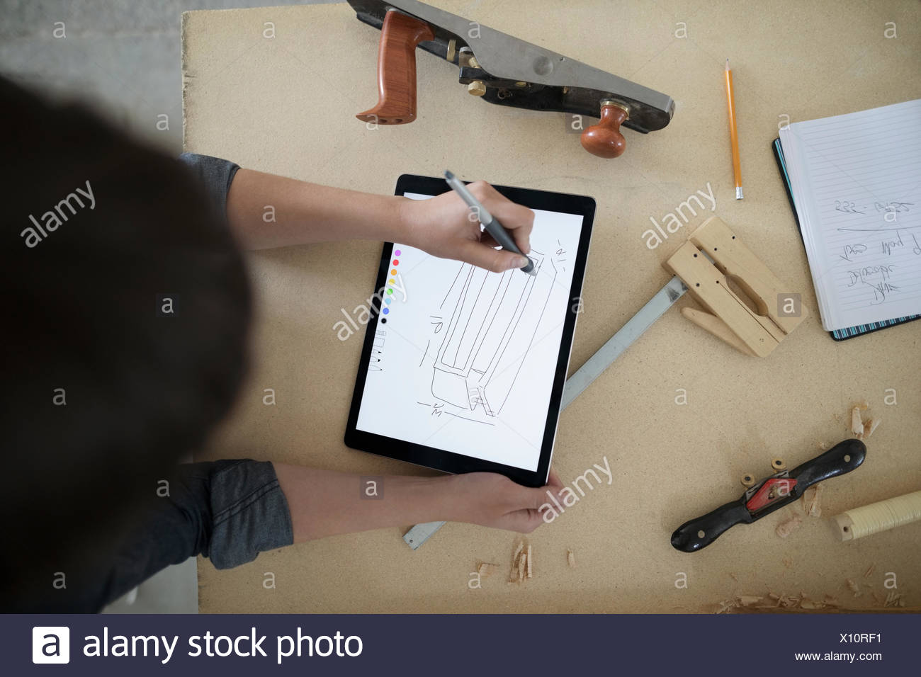 View from above female carpenter sketching with digital tablet stylus at workbench in workshop - Stock Image