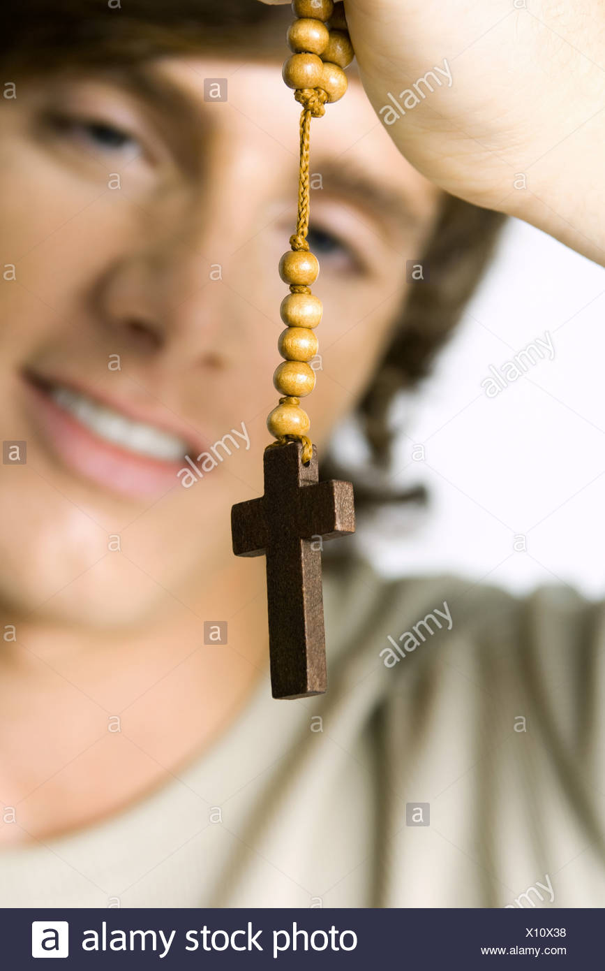 Man holding wooden rosary, focus on foreground - Stock Image
